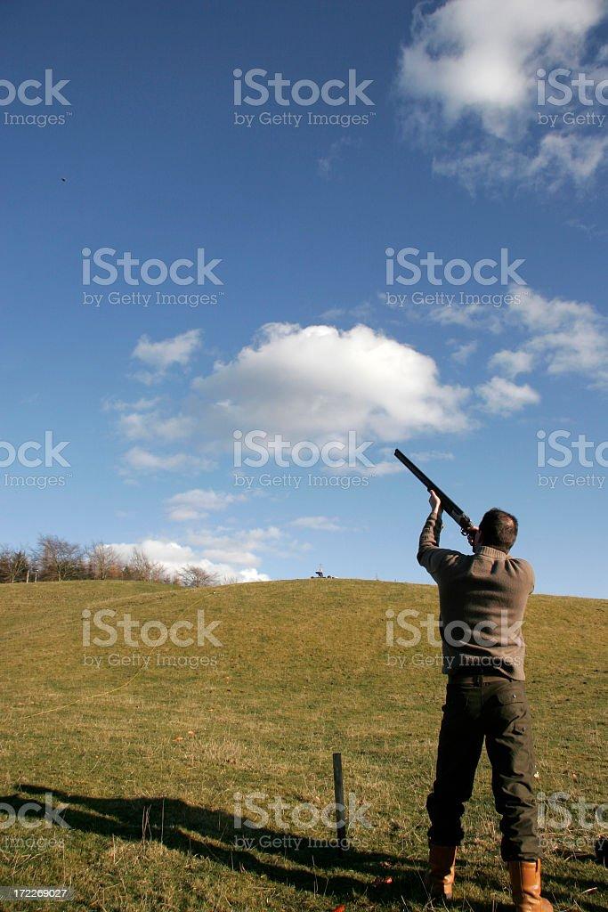 A man aiming and shooting at clay pigeons stock photo