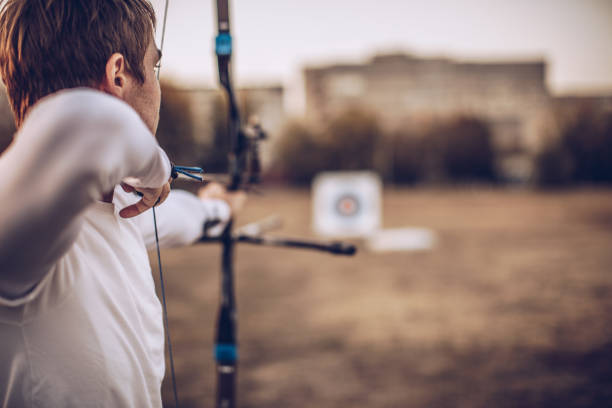 Man aiming at target One man, young archer with bow and arrow training alone outdoors. sports target stock pictures, royalty-free photos & images