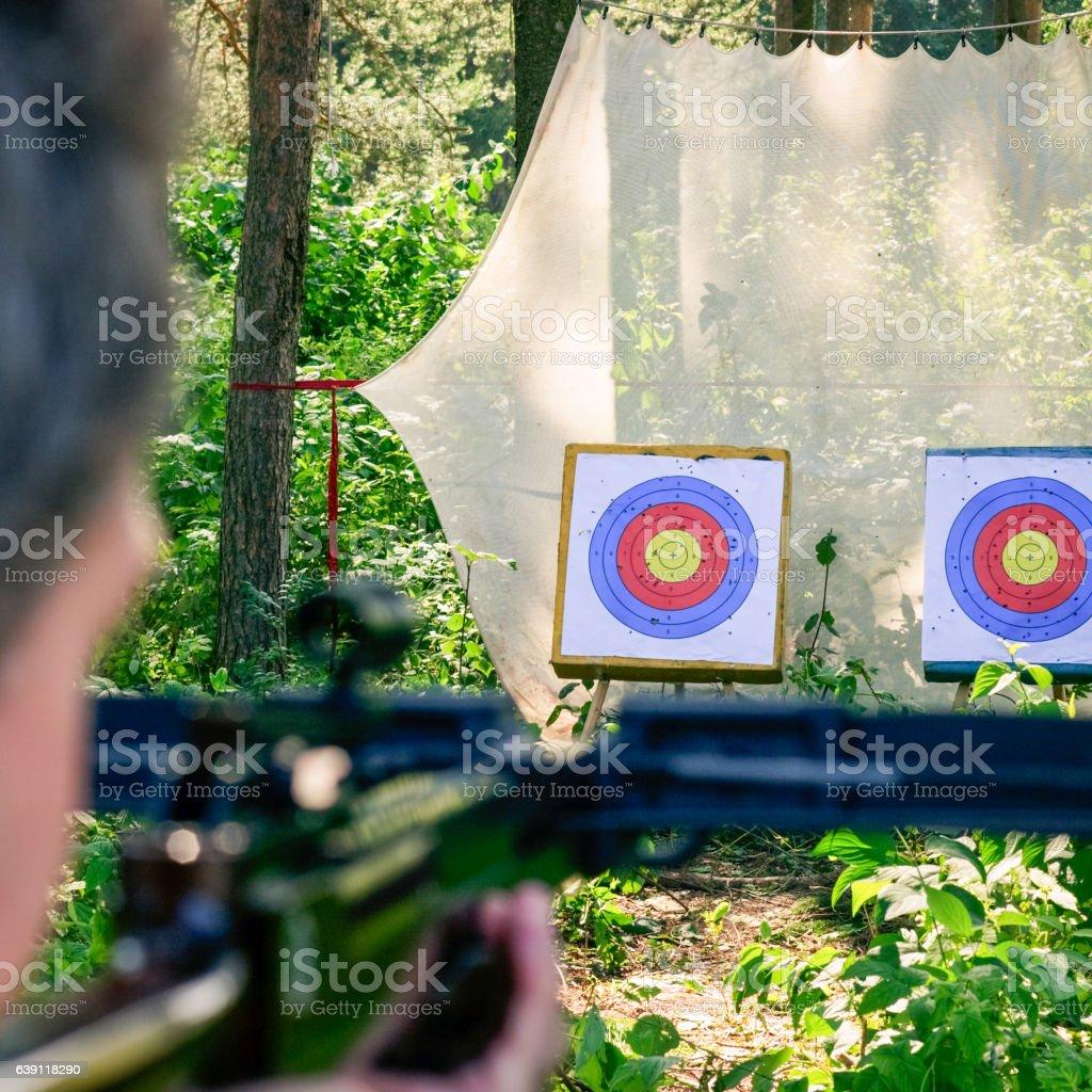 Man aiming crossbow at target - Photo