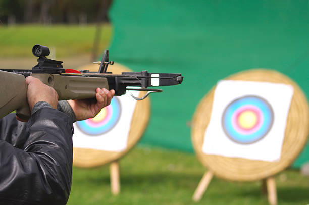 man aiming crossbow at targets - crossbow stock pictures, royalty-free photos & images