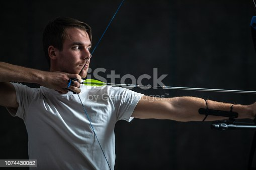 Handsome man aiming with bow and arrow, side view