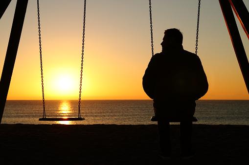 Hombre Solo En Un Columpio Mirando El Asiento Vacío Foto de stock y más  banco de imágenes de Actitud - iStock
