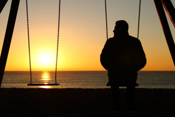 man ensam på en swing tittar på tomma sätet - dog bildbanksfoton och bilder