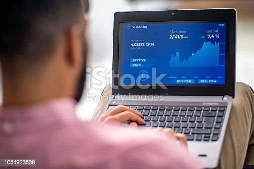 istock Man analyzing financial chart on his laptop 1054923536
