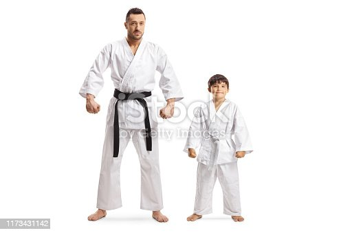 Full length portrait of a man and a boy in karate kimonos isolated on white background