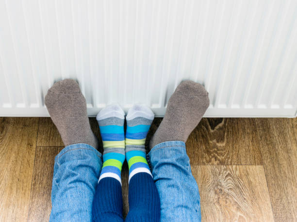 a man and a child in winter socks warm their feet near the heater. - warm house stock photos and pictures