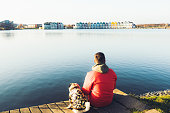 Young man in red jacket and his small dog - pug breed in yellow jacket sitting on the pier near the lake looking at the colorful houses during sunny day in Netherlands