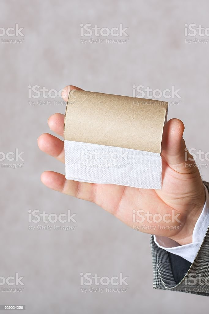 Man and a finished toilet paper roll stock photo