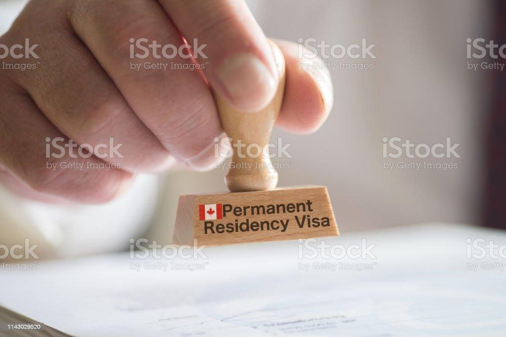 Een man en een stempel voor een visum voor Canada - Royalty-free Canada Stockfoto