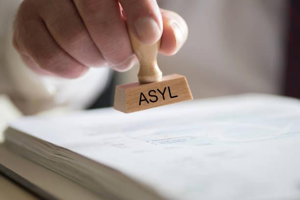 A Man and a Stamp with the Imprint Asylum Ein Mann und ein Stempel mit dem Aufdruck Asyl civil servant stock pictures, royalty-free photos & images