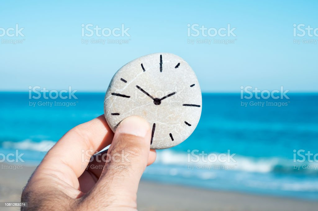 man and a stone with a clock drawn in it stock photo