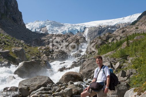 Man and a waterfall (Buarbreen glacier, Folgefonna National Park, Norway)