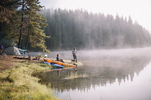 Man and woman are having fun fishing at the mountains