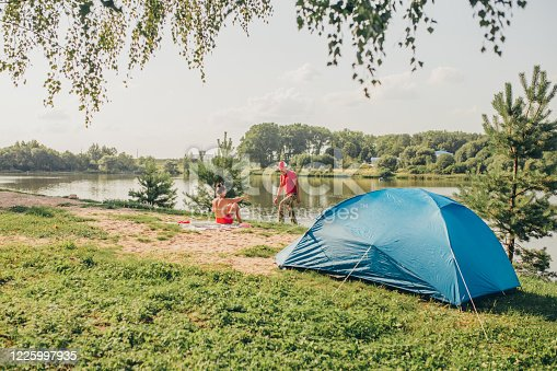 The man and the woman have a rest on the river bank with a tent - a hiking trip - a vacation in the country alone with nature