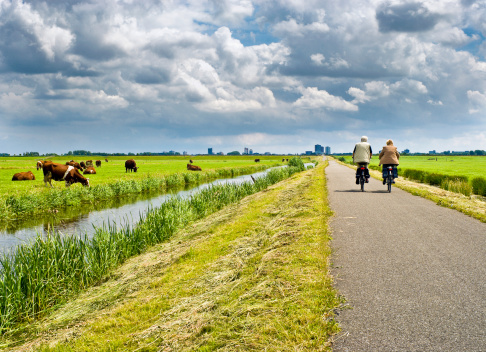 A man and a woman cycling on a road with green surroundings