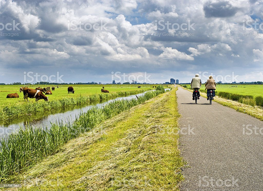 A man and a woman cycling on a road with green surroundings stock photo