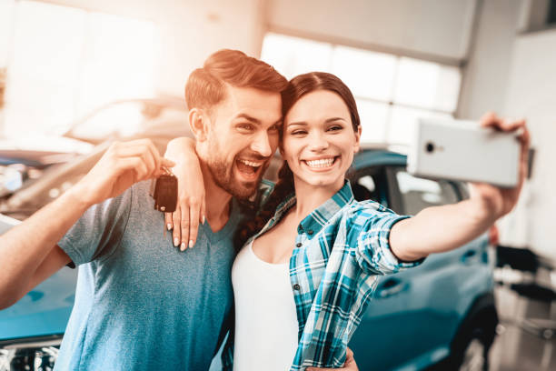 A Man And A Woman Do Selfie Near Their New Car. stock photo