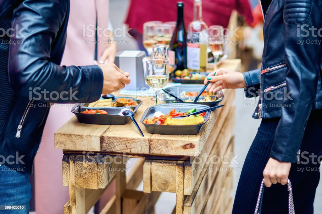 A man and a woman eat street food. Pilaf and mussels stock photo