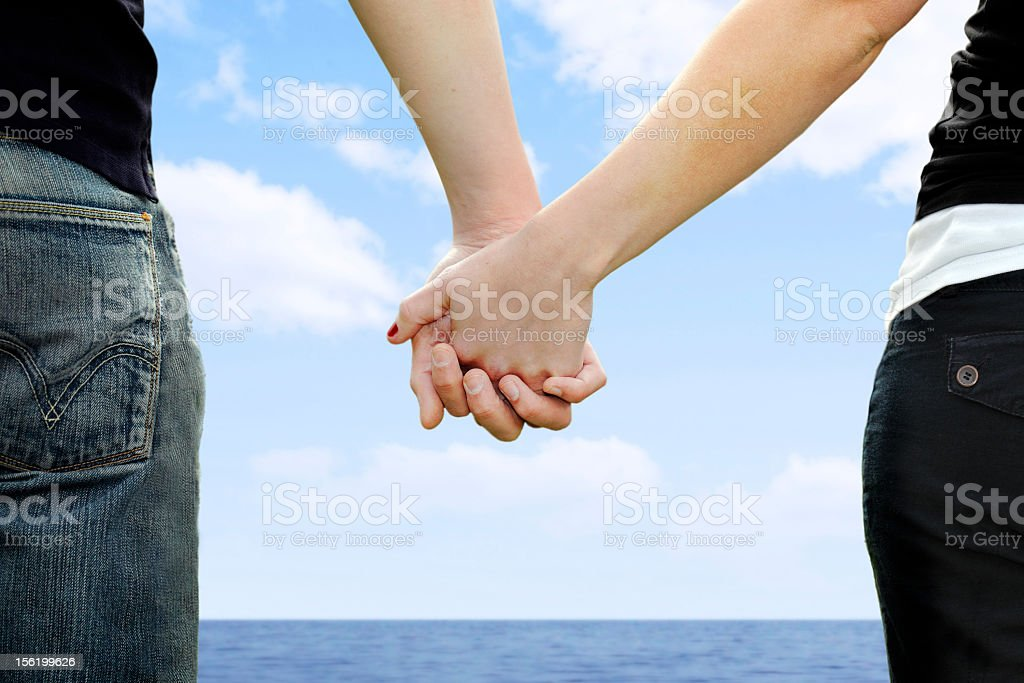 A man and a woman holding hands in front of a body of water royalty-free stock photo
