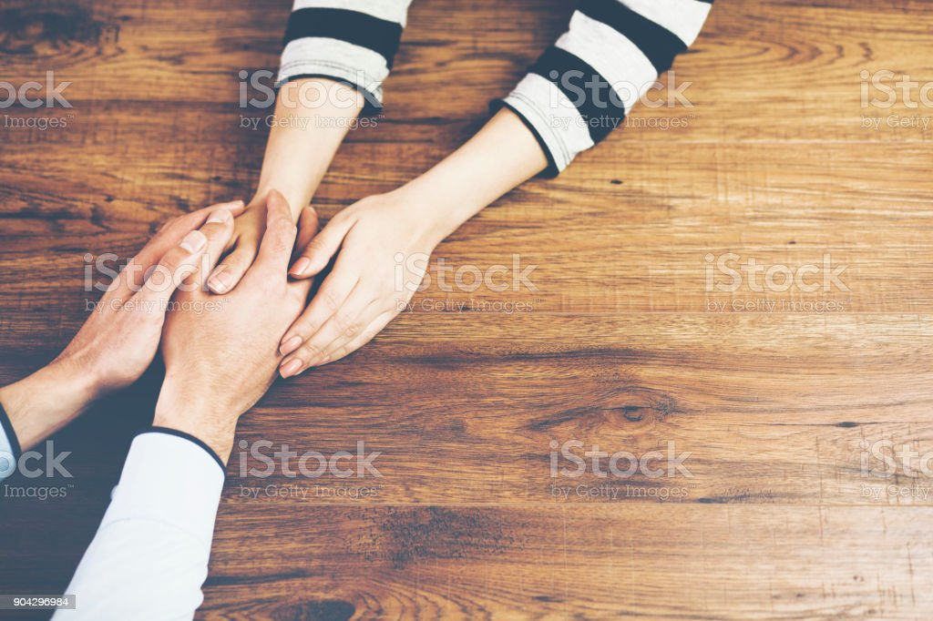 man and a woman holding hands stock photo
