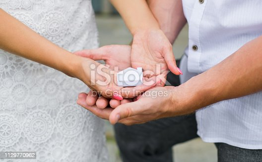 istock A man and a woman holding in their hands a small house. Close up. Horizontal photography 1129770962