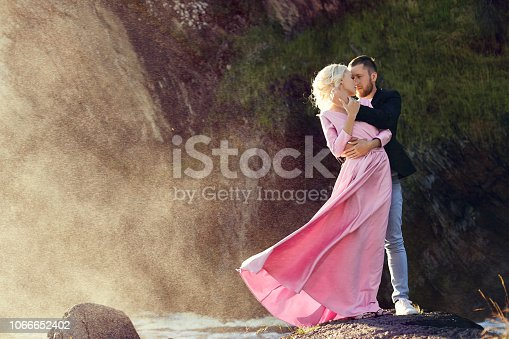 Man and a woman hugging in the summer at sunset in beautiful clothes. Couple in love stands on the shore on the rocks in the sun, hugging and kissing in the splashes of water. Pink dress