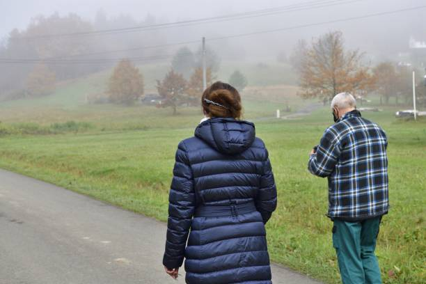 A man and a woman in protective masks on their faces walk in nature stock photo