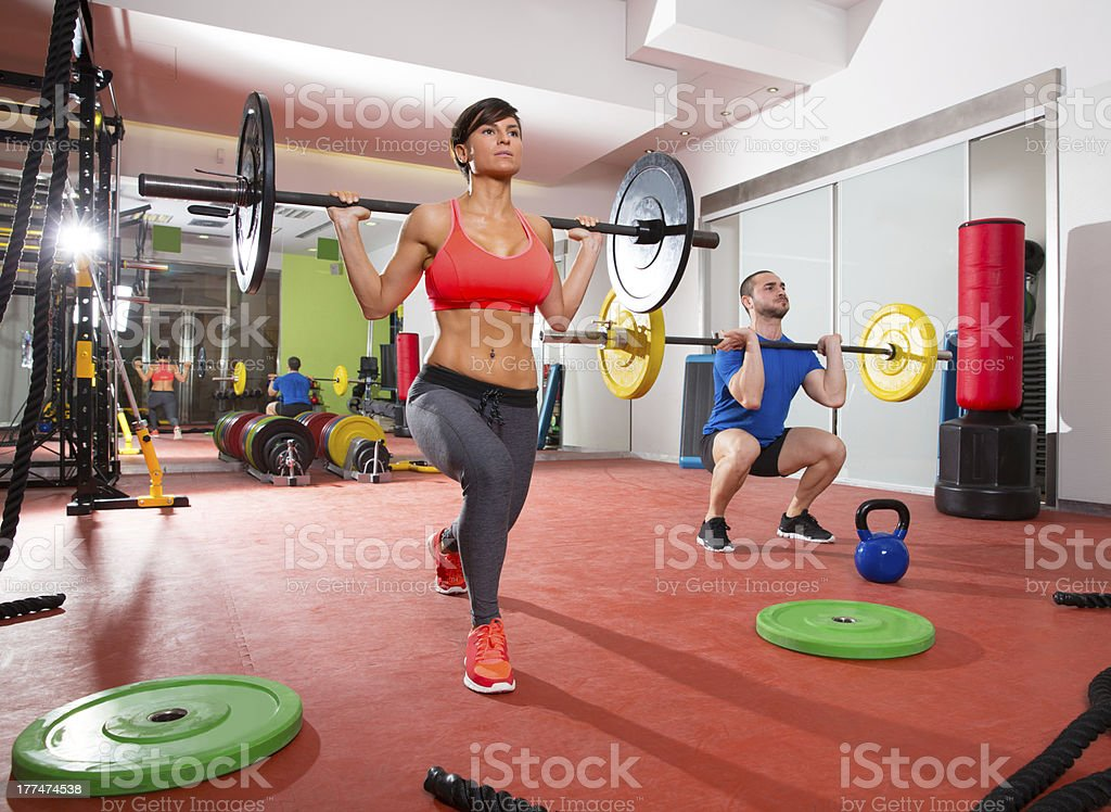 A man and a woman lifting weights in a fitness gym royalty-free stock photo