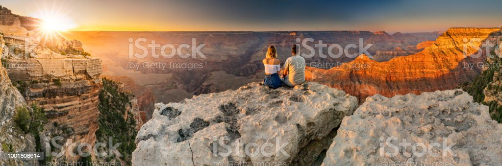 A man and a woman sit at the edge of the Grand Canyon at sunset minutes royalty-free stock photo