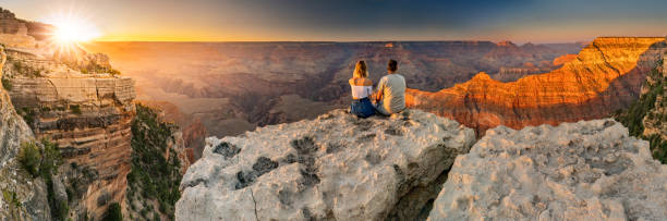 A man and a woman sit at the edge of the Grand Canyon at sunset minutes stock photo