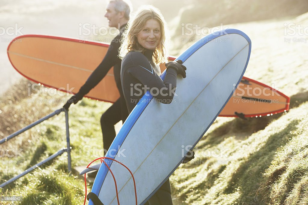 A man and a woman with surfboards stock photo