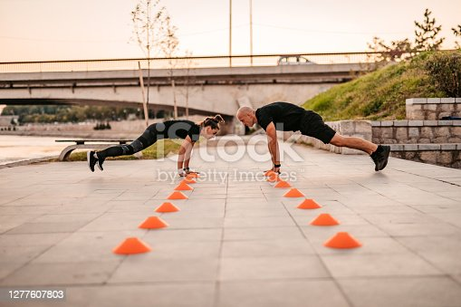 Young athlete man and a woman working out at sunset by the river.