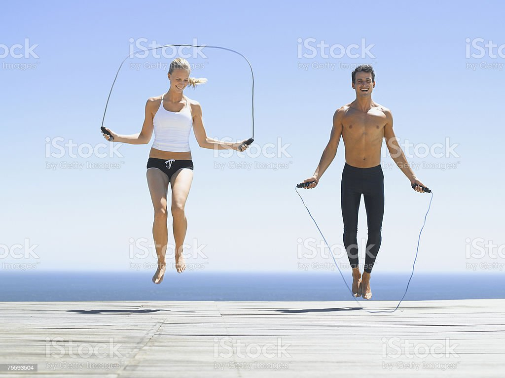 A man and a woman working out with jump ropes stock photo