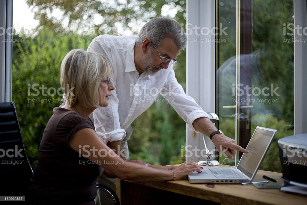 A man and a woman working together and pointing at a laptop royalty-free stock photo