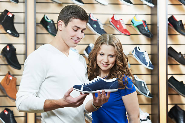 man and assistant at shoe shopping stock photo