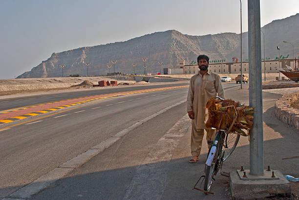 Man and bicycle roadside Khasab, Oman stock photo