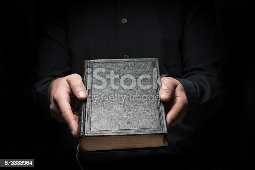 istock Man and black hardcover book 873333964