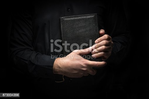istock Man and black hardcover book 873334356