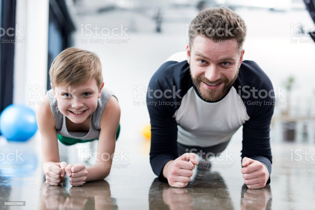 Man and boy doing plank exercise at fitness center stock photo