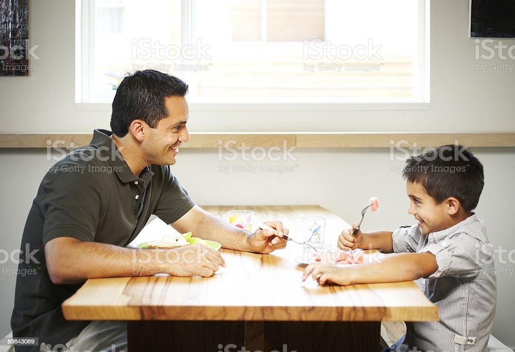 man and boy eating royalty free stockfoto