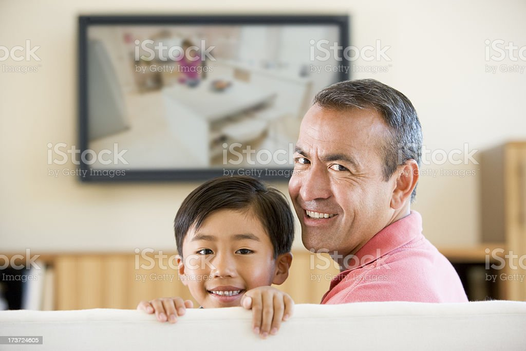 Man and boy in living room with flat screen tv behind them royalty-free stock photo