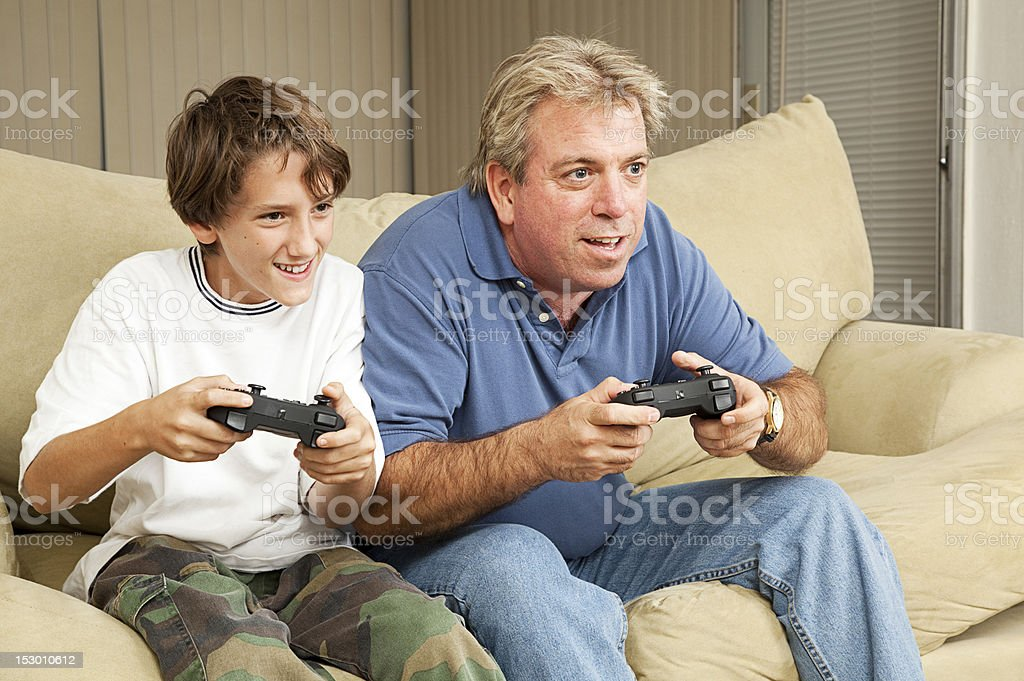 Man and Boy Play Video Games stock photo