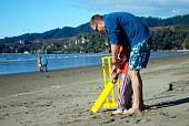 istock Man and Boy Playing Cricket on Beach 497384012