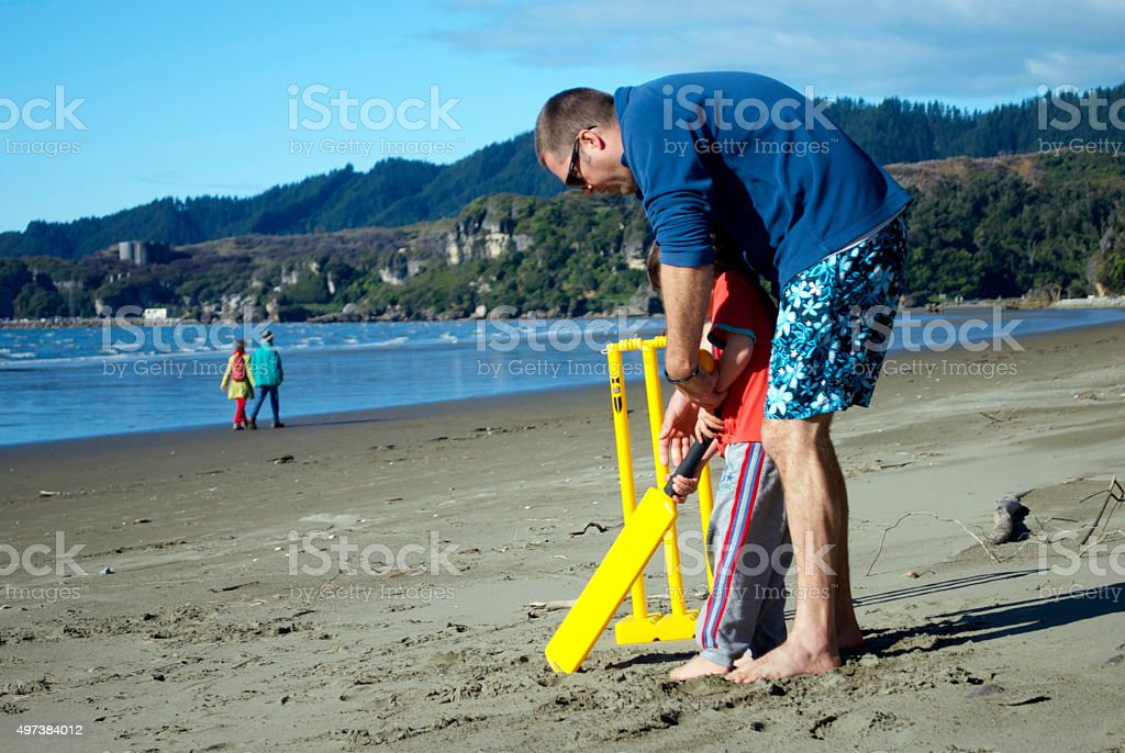 Man and Boy Playing Cricket on Beach stock photo