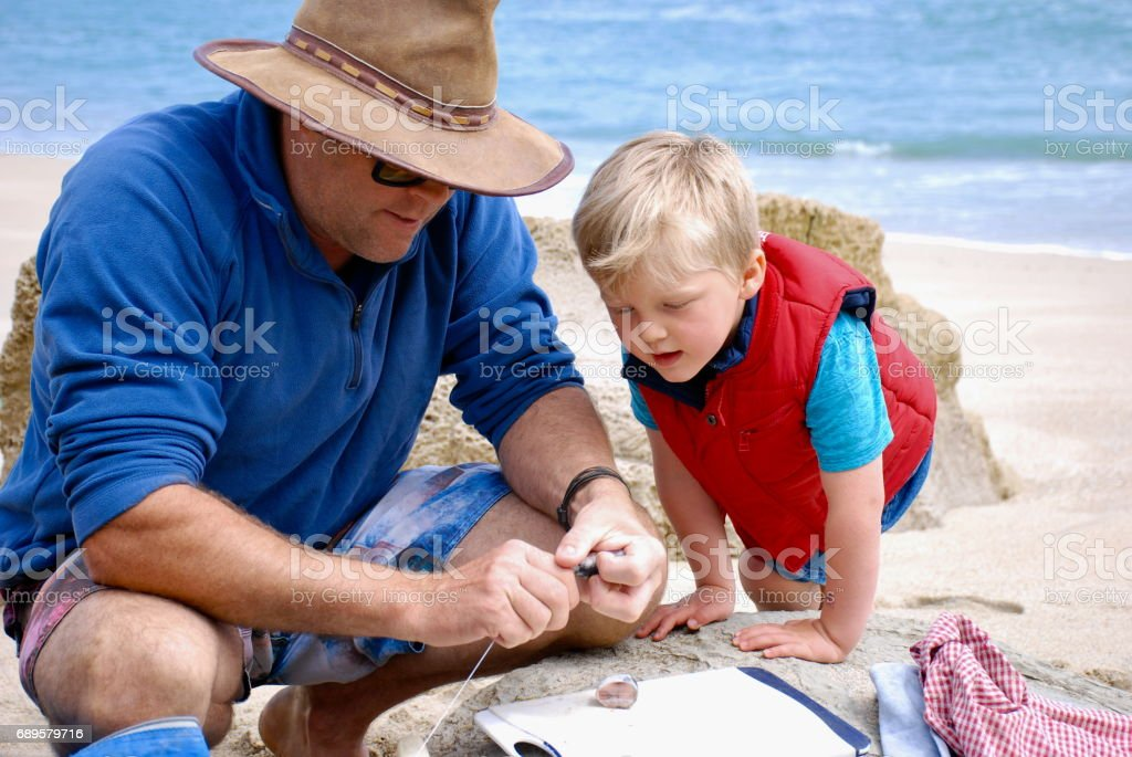 Man and Boy prepare bait for Surf Fishing in Summer stock photo
