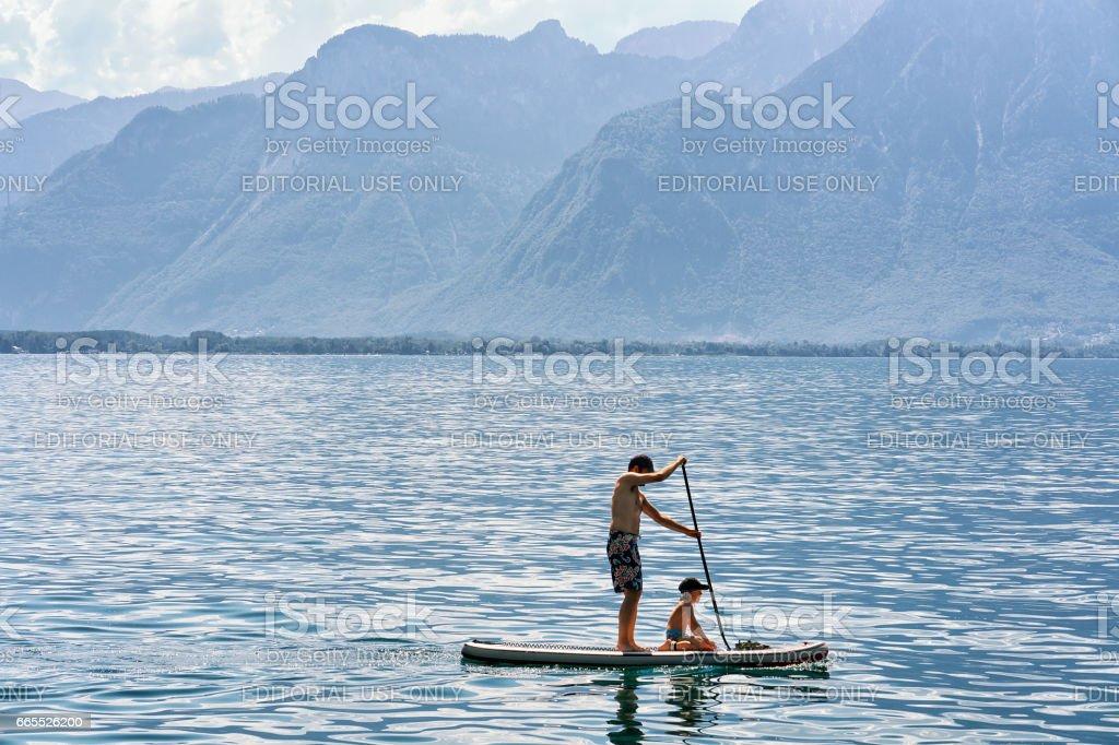 Man and boy Standup paddle board on Geneva Lake Montreux stock photo