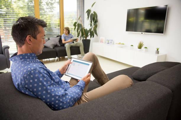 man and boy using digital tablet - tv e familia e ecrã imagens e fotografias de stock