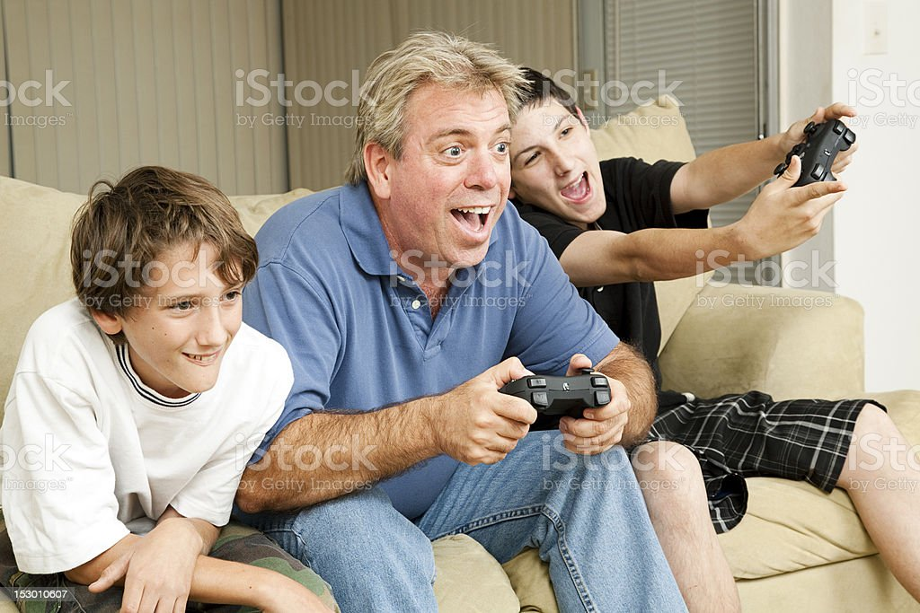 Man and boys playing video games stock photo