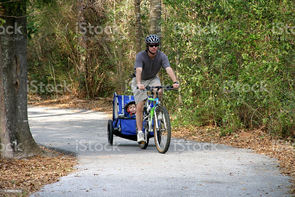 man and child bike riding stock photo