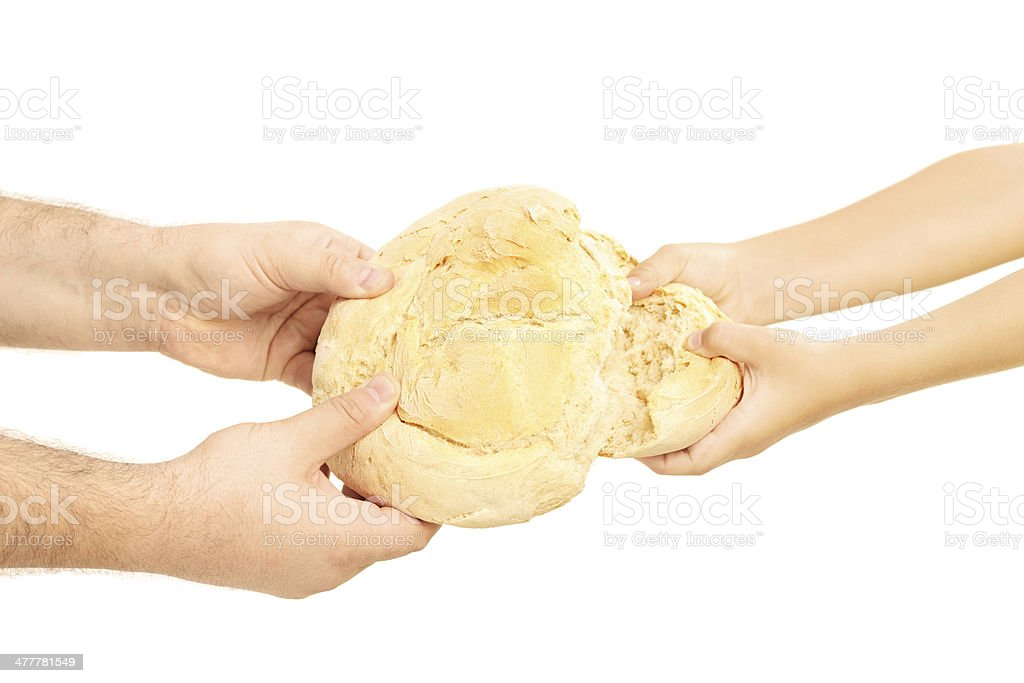 Man and child breaking apart a bread loaf stock photo
